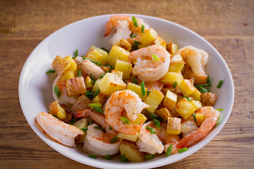 Shrimps with scallions and crispy potatoes in white bowl on wooden background. horizontal