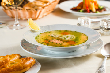 Fresh fish soup in a white plate with specialties and sauces and homemade bread
