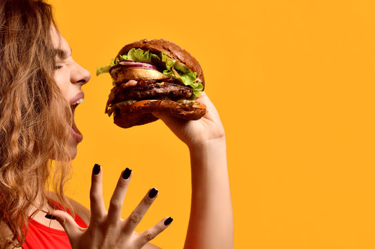 Woman hold big beef burger sandwich with hungry mouth happy screaming laughing on yellow background