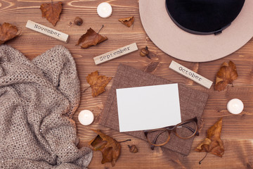 Autumn composition. Flat lay, top view. Hat, scarf, glasses, bouquet of flowers, diary, candles, leaves on a wooden background with a blank sheet and space for text