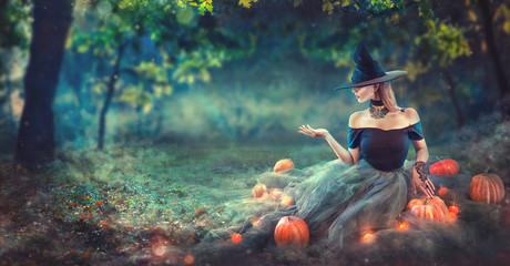 Halloween Witch with a carved pumpkin and magic lights in a dark forest at night. Beautiful young woman in witches costume pointing hand