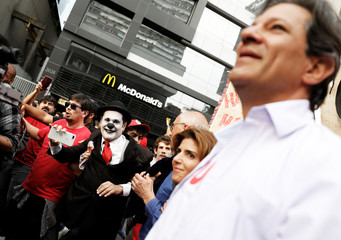 Man dressed as a clown records to presidential candidate Haddad of the Workers Party during a campaign rally in Sao Paulo