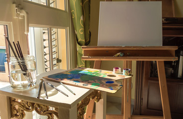 Materials ready to paint next to a bright window: blank canvas on an easel, used palette, brushes and paint. Place to work at home.