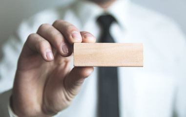 Man holding blank wooden block. Business concept
