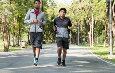 Two men of different ages jogging together in park. People running exercises outdoors to maintain health on nature background. Sport healthy concept.
