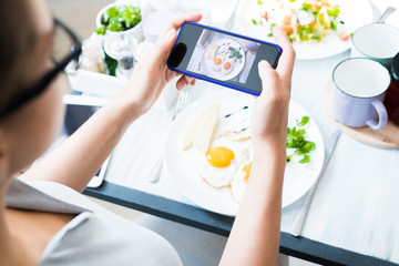 High angle closeup of unrecognizable young woman taking photo of beautiful food via smartphone while enjoying lunch in cafe, copy space