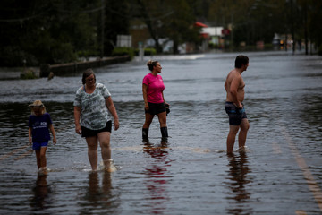 People walk along a flooded street after the passage of tropical storm Florence in New Bern