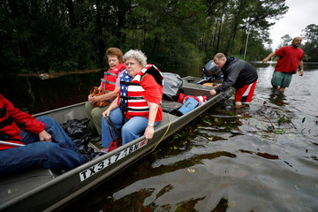 Betty Combs holds onto the boat's rail as she is rescued with her sister Virginia Mobley from rising flood waters in the aftermath of Hurricane Florence in Leland
