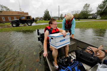 Carla Ramm weeps as her boat is pushed out into the flood waters during her rescue from the church where she has been sheltering for the past four days from the effects of Hurricane Florence, in Leland, North Carolina