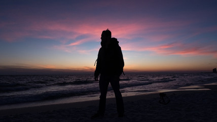 Guy stands in front of dramatic sunset over the ocean on a beach covered with waves.
