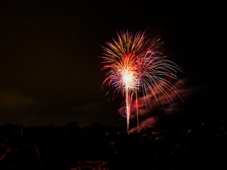 Beautiful vibrant and colorful red, purple, pink and white fourth of July independence day celebratory fireworks exploding in the black night sky.