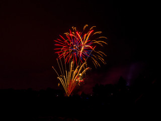 Beautiful vibrant and colorful red and orange floral shaped fourth of July independence day celebratory fireworks exploding in the black night sky.