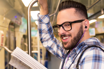 Student traveler with glasses reading book while riding to school by subway train. Concept of commute, effort, aspirations.