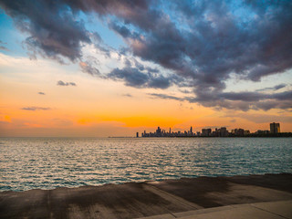 Gorgeous blue and orange colored sunset over the skyline of Chicago with the water of Lake Michigan Below and fluffy clouds in the sky above from Montrose Beach.
