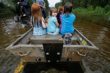 Iva Williamson, 4 years old, peers behind her as she joins neighbors and pets in fleeing rising flood waters in the aftermath of Hurricane Florence in Leland, North Carolina