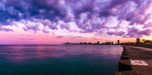 Beautiful panorama photograph of the Chicago skyline at sunset with fluffy purple and pink clouds in the sky above and blue water below along the concrete shoreline at Montrose Beach.