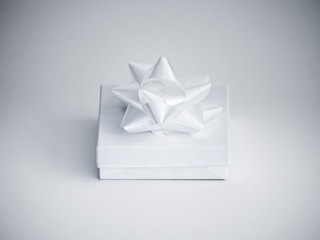 Close-up photograph of a small white glossy gift box with a manufactured shiny white ribbon bow on top isolated on a white background.