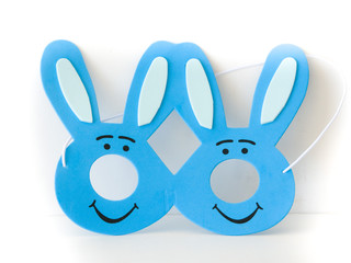 Cute photograph of a child's dark and light blue Easter bunny mask with ears isolated on a white background making a great holiday background.