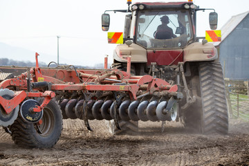 A farmer turns his red tractor and plough at the end of the field