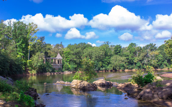 River view of a castle overlook on the Ocmolgee River in Macon, Georgia at Amerson Park with white puffy clouds and blue sky