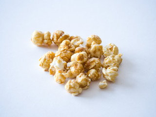 Close up macro photograph of isolated pile caramel popped popcorn kernel pieces at center of image with white space below for delicious looking background or wallpaper image.