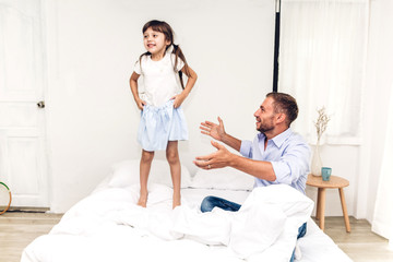 Father with little daughter having fun and playing together on the bed at home.Love of family and father day concept