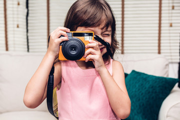 Little cute girl taking a picture with vintage camera at home