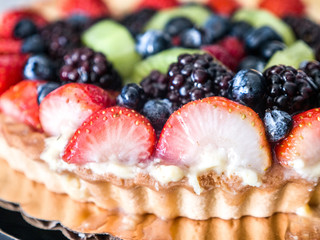 Closeup photograph of a beautiful and colorful vibrant fruit tart dessert with blueberry, strawberry, kiwi and blackberry fruit topping and browned fluted crust edge set on a kitchen counter top.