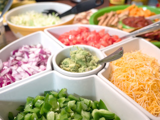 Close up photograph of a white serving tray filled with taco appetizer toppings including cheese, peppers, onion, tomato, guacamole making great background for football party or birthday celebrations.