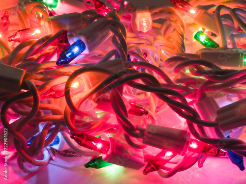 close up photograph of a pile of colored christmas lights including green blue red