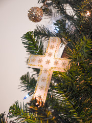 Closeup photograph of a beautiful homemade white and gold cross Christmas ornament hung from an artificial douglas fir Christmas tree lit with lights for a gorgeous religious holiday background