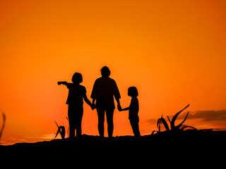 Silhouette of mother with her two daughters looking at sunset sky