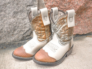 A closeup of a pair of weathered child's cowboy boots with brown and white leather and decorative stitching with field stone background.