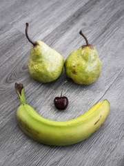 Smiley face composed with ripe fruit including banana for mouth, cherry nose, and two pears for eyes on a gray wood textured background