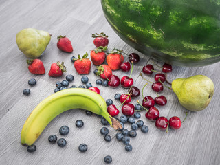 Sharp, vivid photograph of a watermelon, banana, cherries, strawberries, blueberries, and pear fruit randomly scattered on a gray colored wood textured background