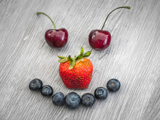 Silly smiley face composed with ripe fruit including cherry eyes, strawberry nose, and blueberry mouth on a gray wood textured background
