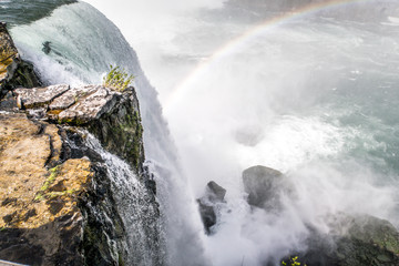 Beautiful view looking over the edge of Niagara Falls waterfall with rainbow forming in the mist below as water hits the boulders below with rocky cliff edge in foreground