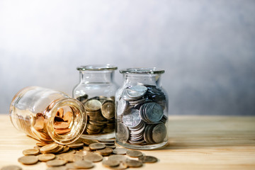 Coins in currency glass jars and spilling on wooden table. Saving money for future retirement. Financial business investment concept