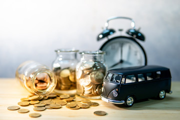 Black car model with gold coin in currency glass jar and clock on wooden table. Car loan interest rate. Saving money for auto buying. Automobile business concept