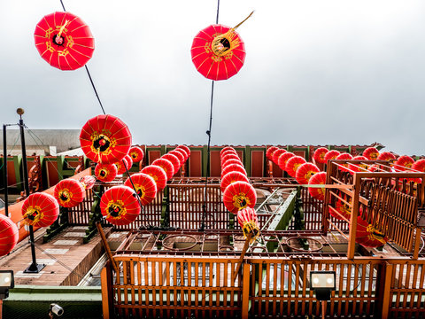Looking up at bottoms of red oriental chinese lanterns with gold colored ornamentation hang from the side of a building fire escape in Chinatown in San Francisco California.