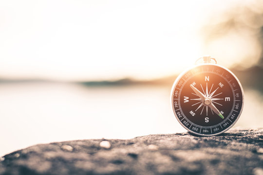 Compass of tourists on mountain at sunset sky.
