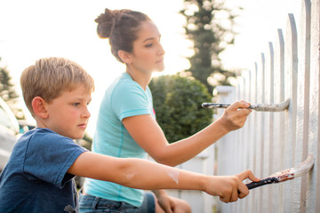 mother and son painting a white picket fence in the summer