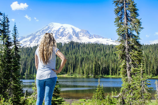 A woman hiking near a beautiful scenic mountain lake at Mount Rainier National Park in Washington USA. Looking up at the snow capped glacier during a day hike