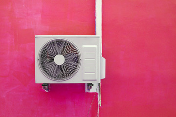 Air conditioning compressor near the pink wall background