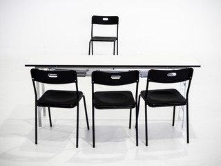 Black chairs with white table on white background. Interview place concept