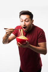 Indian/asian man eating hot noodles or ramen in a Red bowl with chopsticks