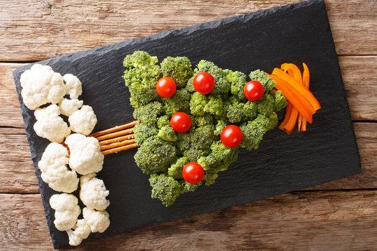 Christmas tree of broccoli, cauliflower, tomato, pepper closeup on table. Vegetarian. Horizontal top view