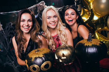 Which pumpkin is more scary? Beautiful young women in evening gown looking at camera and holding pumpkins with smile while celebrating Halloween in nightclub Wall mural