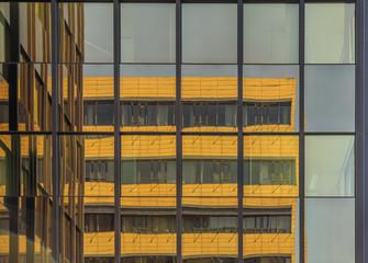Spiegelung eines Bürogebäudes in einer Glasfassade