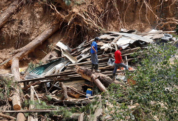 Residents look for missing relatives among debris and destroyed houses at the site of a landslide in Itogon
